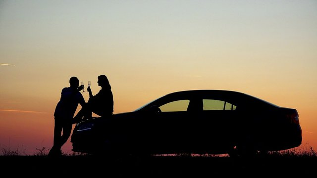 Couple of lovers silhouette drink champagne at sunset, woman sit on car, romantic evening