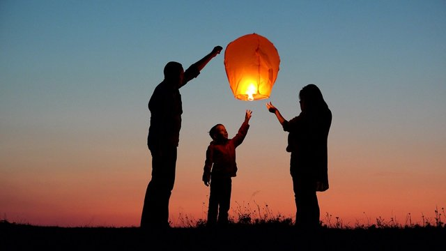 Parents, child and baby silhouette rising lightning sky lantern, conceptual release hope, free dreams of happy family