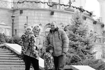 Mom and dad with two children walking outdoor, warm weather. Lifestyle portrait parents and kids in happiness at the outside, moments of life
