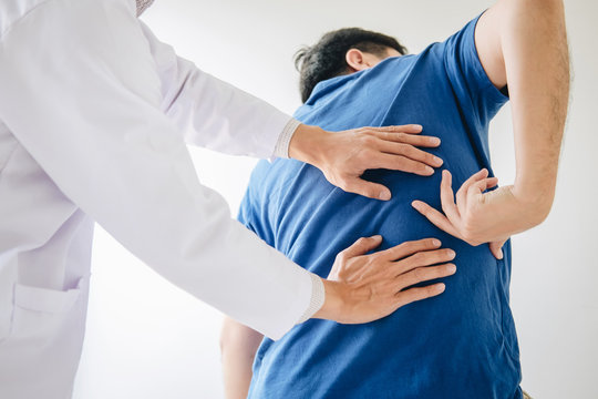 Doctor physiotherapist treating lower back pain patient after exercising