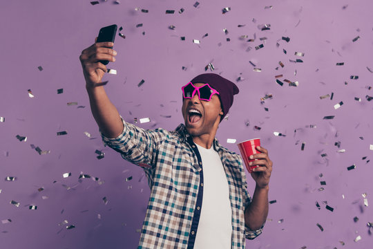 Close up photo portrait of screaming carefree handsome positive with red plastic glass beverage in hands making selfie on device isolated glitter sparkles background