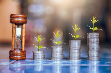 step of coins stacks and tree growing on top with sandglass or hourglass, saving and investment or family planning concept, motion blured background.