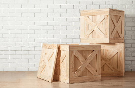 Wooden crates on floor near brick wall, space for text