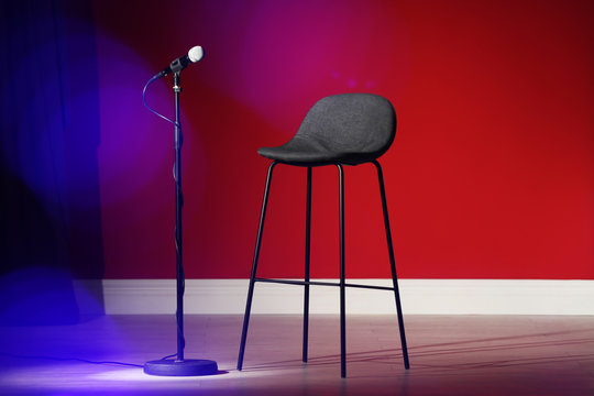 Microphone and stool on stage against color wall. Blurred lights