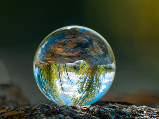Landscape reflected in a crystal ball on an old wooden table