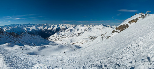 Wall Mural - Panoramic view down snow covered valley in alpine mountain range