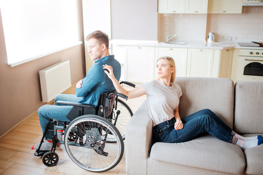 Young man with special needs sit on wheelchair back to back with woman. She touch his shoulder with hand and look at him. Upset and unhappy couple.