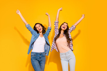 Wall Mural - Portrait of cute pretty hipsters have free time weekends holidays raise arms hands scream shout laugh excited content wear fashionable plaid clothing isolated yellow background