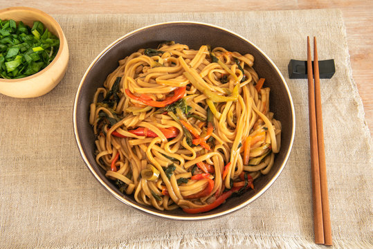 Traditional Chinese vegetarian noodles lo mein on a plate with chopsticks, top view
