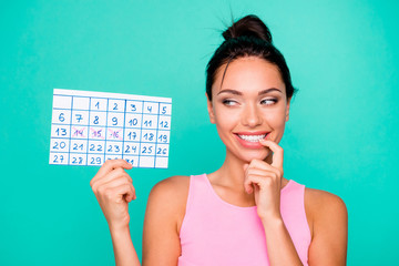 Close up photo beautiful amazing she her lady funny hairstyle bite finger hold hand arm paper calendar birthday party coming tricky mood wear casual pink tank-top isolated teal turquoise background Wall mural
