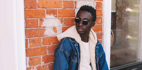 Wall Mural - Fashion close-up portrait african man wearing jeans jacket on city street over brick textured wall background