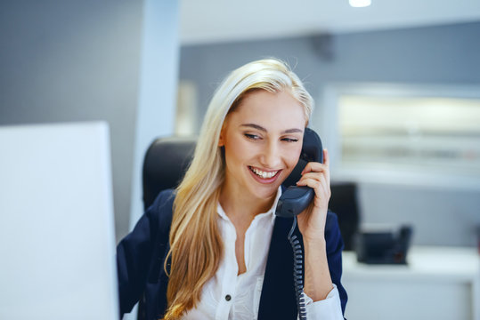 Smiling beautiful Caucasian businesswoman having phone call while sitting in office. Great minds think independently, not alike.