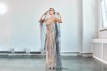 Portrait of professional ballet dancer in flowing fabric dress and veil on head, dancing at the performance. Art concept.