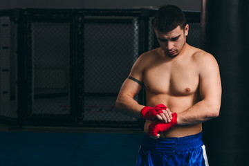 Young shirtless male boxer in blue sport shorts wraps his knuckles with elastic bandage, on dark background.
