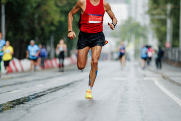 Fototapete - male runner leader of city marathon race run in rain