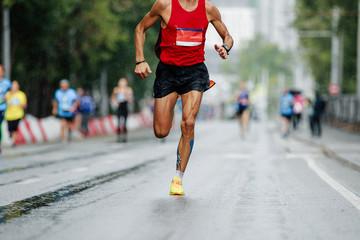 Wall Mural - male runner leader of city marathon race run in rain