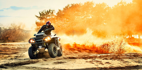 Teen riding ATV in sand dunes making a turn in the sand Fototapete