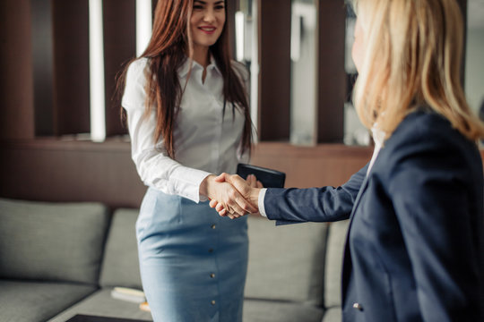 Two caucasian businesswomen in office clothes shaking hands at the meeting as they close a partnership, focus on hands
