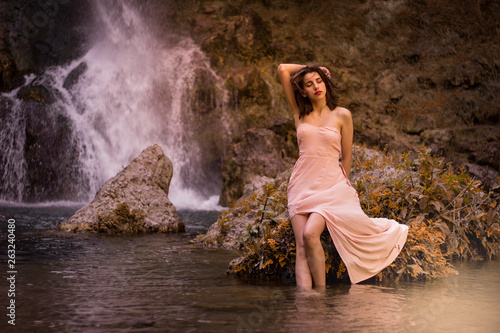 Attractive girl posing on the rock among in fairy fast