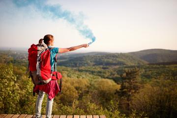 Female mountaineer sending smoke signal to hikers group