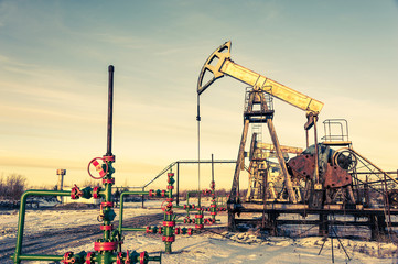 Oil pump jack and wellhead on an oil field. Mining and petroleum industry. Power generation concept.