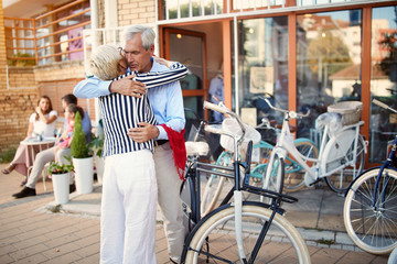 Elderly couple buying new bicycle in bike shop.