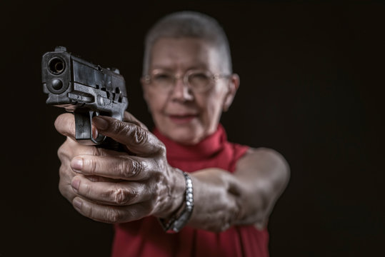 Classy undercover agent, a senior old woman aiming a gun, policewoman or a secret agent
