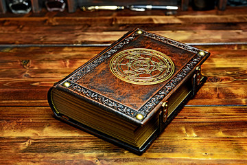 Vintage Alchemist book with gilded paper edges and the symbol lay down to the wooden table in the dark atmosphere