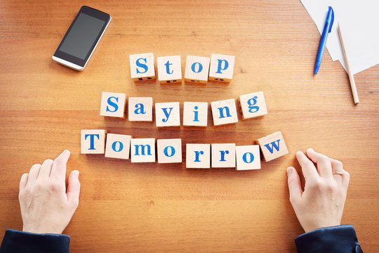 Stop saying tomorrow. Business woman made text from wooden cubes on a desk