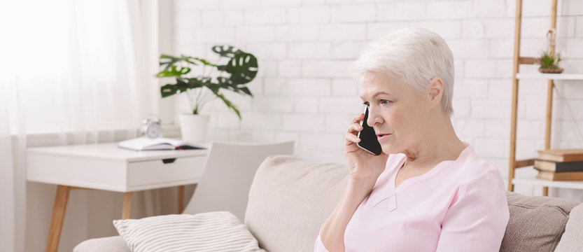 Unhappy worried senior woman talking on phone
