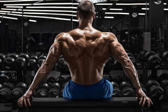 Rear view muscular man showing back muscles at the gym. Strong male naked torso, workout