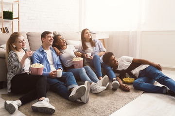 Comedy film. Happy friends watching movie at home