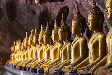 Buddha statue with light shinning through cave at Khao luang, Phetchaburi Province in Thailand.