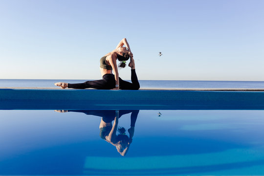 Young attractive woman practicing yoga doing Monkey God exercise, Splits, Hanumanasana pose, working out by the pool, above the beach, relaxing against blue sky. Health and beauty concept. Copy space