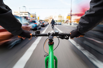 Cyclist drives on the bike path past the traffic jam - First-person view of cyclist/ motion blur