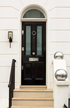 Black Wooden Entrance Door to residential building in London. Typical door in the English style.