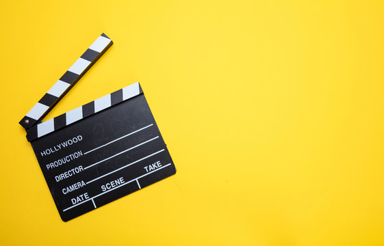 Movie clapperboard on yellow color background, top view