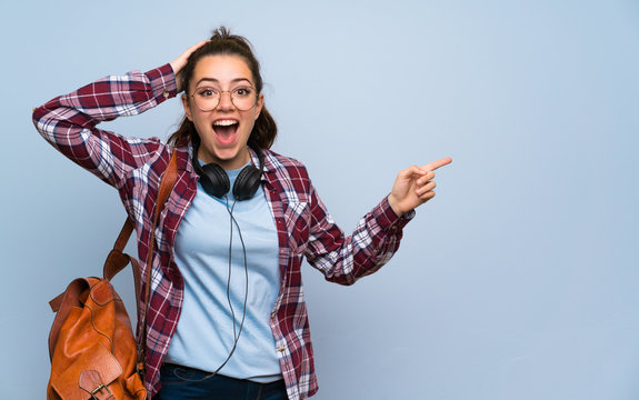 Teenager student girl over isolated blue wall surprised and pointing finger to the side