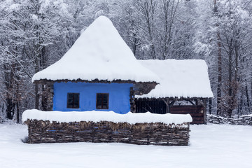 Traditional blue house in the Village Museum during a snowy winter