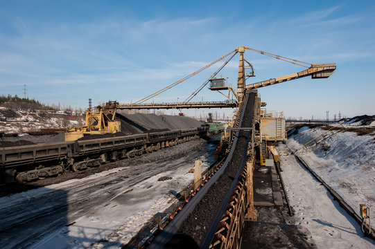 delivery of iron ore by a conveyor belt from a warehouse and loading into railway dump cars.