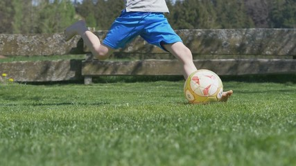 2a7432b93 0 20 playing soccer in garden - slow motion of young boy kicking a football