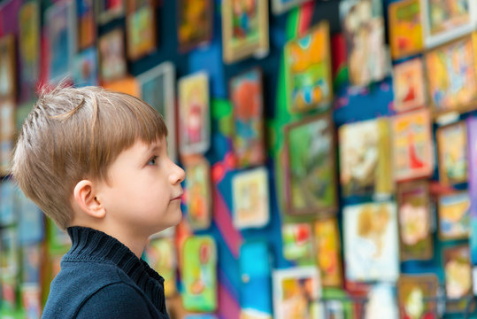 The boy looks at the paintings at the exhibition of pictorial art and creativity.