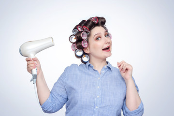 Young happy girl in a striped shirt with hair curlers on her head and a hairdryer
