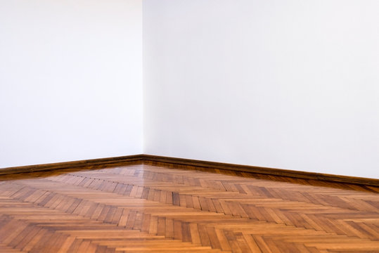 Clean empty room corner with white walls and a wooden parquet floor