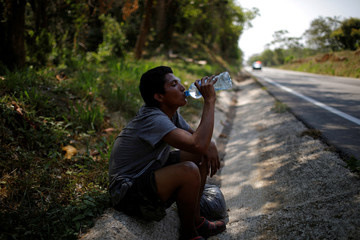 A central American drinks water on a roadside due to dehydration during his journey towards the United States, in Mapastepec