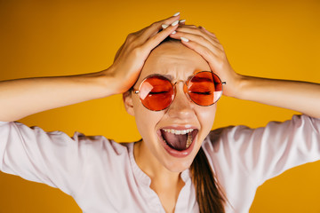 The girl in the shirt and hipster red glasses screams and holds her head. A tired office worker wants a vacation. Yellow background