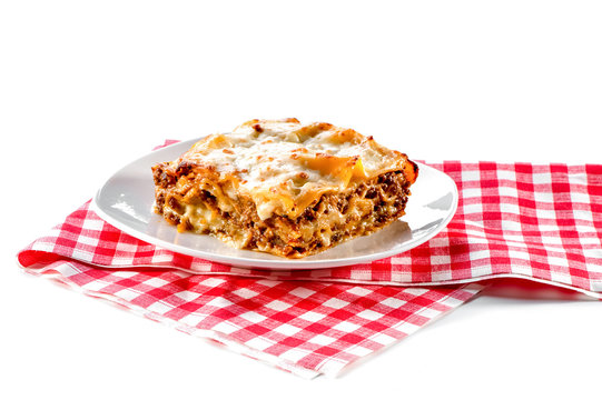 piece of lasagna with plate and checkered red napkin isolated on white background