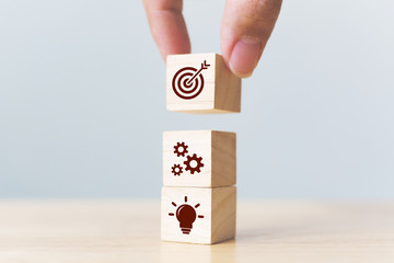 Concept of business strategy and action plan. Businessman hand putting wood cube block on top with icon Wall mural