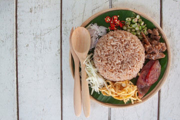 Obraz Rice mixed with shrimp paste Thai people call Kao Cluk Ka Pi on white wooden table. - fototapety do salonu