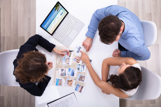 Travel Agent Giving Information To A Young Couple